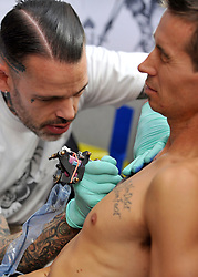 © Licensed to London News Pictures. 23/09/2011. LONDON, UK. A man winces in pain as he has a tattoo imprinted on his chest. The 7th London Tattoo convention takes place today (23 Sept 2011) at the Tobacco Dock in the East End of London. The convention attracts artists and customers from all over the world. It runs until 25th September 2011. Photo credit:  Stephen Simpson/LNP
