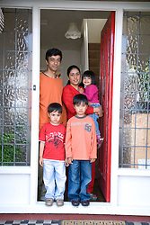 Young family standing outside their front door,