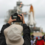A photographer takes photos of the shuttle Atlantis as it sits on the pad after the rotating service structure is peeled away at the Kennedy Space Center Thursday, July 7, 2011, in Cape Canaveral, Fla. (AP Photo/Alex Menendez)