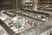 Foil insulated heating system pipes, inside the boiler room of a modern office building in central London UK.
