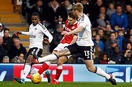Tom Bradshaw of Barnsley © tries a shot at goal but is blocked by  Ryan Sessegnon (L) & Tim Ream of Fulham (R). EFL Skybet championship match, Fulham v Barnsley at Craven Cottage in London on Saturday 23rd December 2017<br /> pic by Steffan Bowen, Andrew Orchard sports photography.