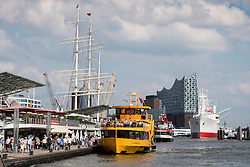 View of busy ferry and tour boat landing jetties, Landungsbrucken, and skyline of city  in port of Hamburg Germany