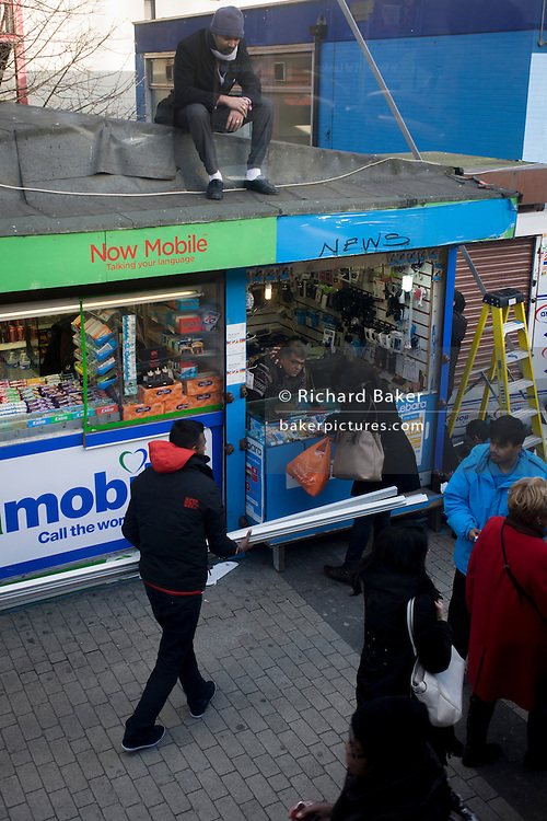 A man sits unnoticed on the roof of a mobile phone provider kiosk at Elephant & Castle in the south London borough of Lambeth.