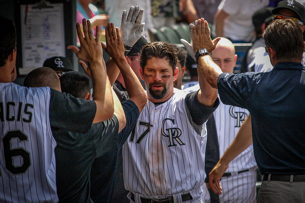 Colorado Rockies first baseman TODD HELTON #17 is greeted in the dugout after tying the game 2-2 in the sixth inning with a solo homer off Minnesota Twins pitcher KEVIN SLOWEY in MLB action.  The Rockies went on to win 6-2.