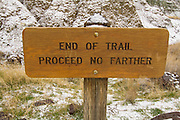 A sign marking the end of the trail at The Blue Basin feature of the John Day Fossil Beds National Monument; Oregon. Formed from 29-million-year-old volcanic tuff, The erosion scarred slopes of these hills are slowly yielding fossils of ancient animals and plants.