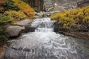 A waterfall tumbles over a granite slab amid fall colors at the outlet of  Black Lake, Rocky Mountain National Park, Colorado.