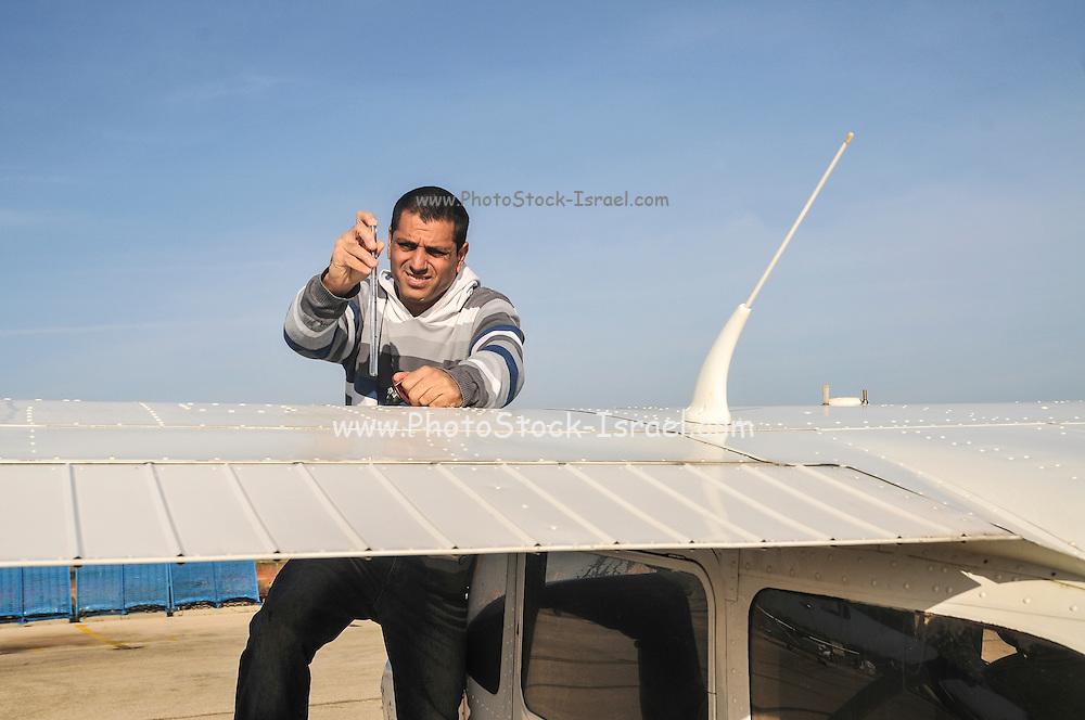 Pilot perform a preflight check and checks the petrol quality on a cessna skyhawk