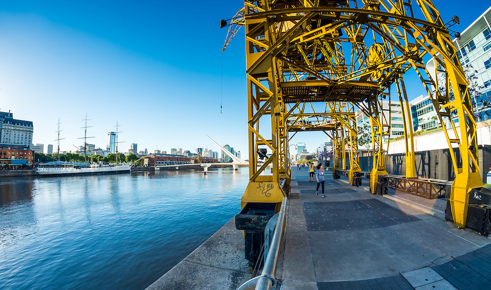 BUENOS AIRES - CIRCA NOVEMBER 2012: View of boardwalk and cranes with La Mujer Bridge in background in the neighborhood of Puerto Madero, circa November 2012. This is a popular tourist destination with over 2.5 million yearly visitors .