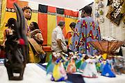 Customers browse items for sale in a stand at the 22nd Salon International de l'Artisanat de Ouagadougou (SIAO) in Ouagadougou, Burkina Faso on Saturday November 1, 2008.