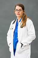 Female medical doctor wearing white lab coat photographed in a stuido