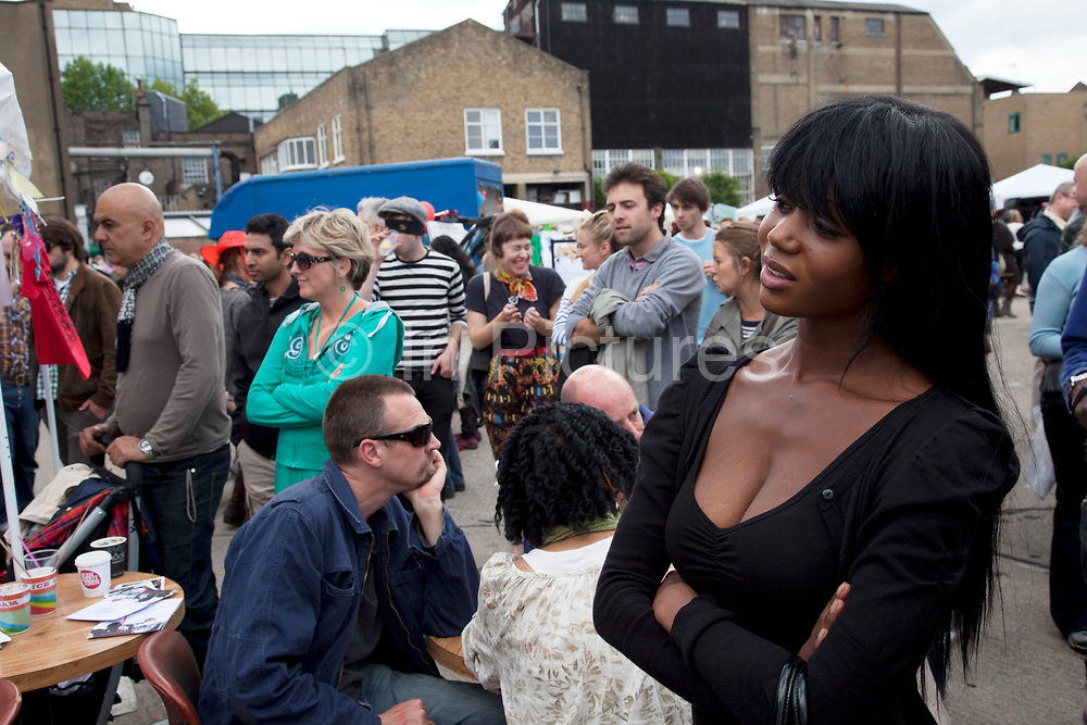 People listening and dancing to a fantastic band playing surf music. The Art Car Boot Fair in a car park just off Brick Lane in East London. This is an alternative art event where artists show their works and engage with the public. The Art Car Boot Fair was an idea that grew out of a desire to re-introduce some summer fun and frivolity into a thriving but increasingly commercial London art scene. The aim for the Art Car Boot Fair is to be a day when the artists let their hair down and for all-comers to engage with art in a totally informal way, and to pick up some real art bargains.
