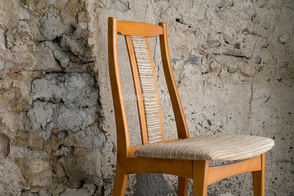 chair against an old stone wall with improvised cement repairs