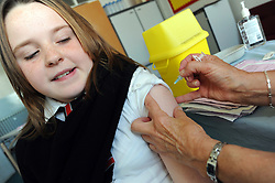 School nurse injecting 12 year old girl with HPV vaccination to immunise against cervical cancer UK