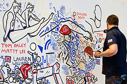 © Licensed to London News Pictures. 27/07/2021. LONDON, UK.  Ben Mosley, an action and expressionist painter, creates a wall mural focused on the achievement of Team Great Britain (GB) athletes at the Tokyo Olympics 2020.  He is currently working from the pop-up Team GB Studio in Carnaby Street until 8th August,and the work is updated daily with athletes' successes.  Team GB has become the first to adopt non-fungible tokens (NFTs) featuring the athletes' previous achievements, which can be purchased through a dedicated store.  Photo credit: Stephen Chung/LNP