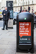A modern waste bin on King William Street, Bank, London, United Kingdom.  The rubbish bin has a digital screen installed and shows news messages.  It displays a message: 'FTSE 100 falls 0.12% at open this morning'.  The bin is located near the Bank of England in the centre of the famous London Square Mile.