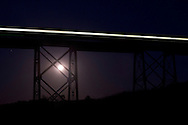 Salisbury Mills - The full moon rises in the background as a train crosses the Moodna Viaduct railroad trestle on Oct. 8, 2014.
