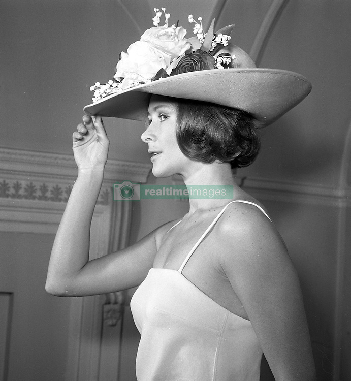 Aldine Honey models a swimsuit and hat at Christian Dior's London boutique.