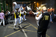 Morris dancers from the Westminster Morris Men, performing outside in Borough Market one Summer evening at people out for an evening drink watch on in London, United Kingdom. The Westminster Morris Men perform with sticks. Morris dance is a form of English folk dance usually accompanied by music. It is based on rhythmic stepping and the execution of choreographed figures by a group of dancers, usually wearing bell pads on their shins. The earliest known and surviving English written mention of Morris dance is dated to 1448.