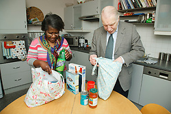Carer and pensioner unloading shopping.