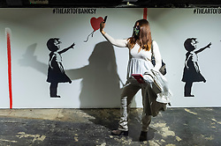 """© Licensed to London News Pictures. 18/05/2021. LONDON, UK. A visitor takes a selfie, in the designated selfie area. Preview of """"The Art of Banksy"""" at Seven Dials, Covent Garden. Over 100 pieces of Banksy's works are on display from private collections across the globe and it is the first time the world's largest touring exhibition of authentic Banksy Artworks has come to the UK, deferred from 2020 due to the coronavirus pandemic but opening now as lockdown restrictions are eased.  The show runs 20 May to 21 November 2021.  Photo credit: Stephen Chung/LNP"""