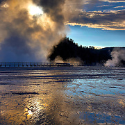 The sun rises behind the steam from Excelsior Geyser, Yellowstone National Park, Wyoming.
