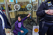 An enviroment protester super glues her hand to the front entrance of Shell oil HQ on 15th April 2019 in London, United Kingdom.  Extinction Rebellion a climate change protest group are protesting  across the centre of London and plan to block traffic for the next five days.