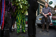 May Day custom of Deptford Jack in the Green, a man encased in a framework entirely covered with greenery, is one of the lesser-known modern revivals by the Blackheath Morris Men of English traditional customs on May 1st 2016 in London, United Kingdom. Climbing into the Jack outside the Dog and Bell pub. Fowlers Troop Jack in the Green was revived in the early 1980s. Originally a revival from about 1906, it developed from the 17th Century custom of milkmaids going out on May Day with the utensils of their trade, decorated with garlands of flowers and piled into a pyramid which they carried on their heads. By the mid eighteenth century other groups, notably chimney sweeps, were moving in on the milkmaids territory as they saw May Day as a good opportunity to collect money, so carried a Jack in the Green. Over the last 25 years several popular festivals have grown up around the Jack in the Green tradition. Deptford Jack in the Green is not very widely known although it has been running since the early 1980s.