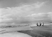 9969-7275. People calling their children in from the surf as the last light on the sun touches the beach at Neskowin, Oregon. July 18, 1948.