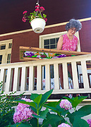 Judy Ballinger paints silk scarf on porch of West Reading house, Berks Co., PA