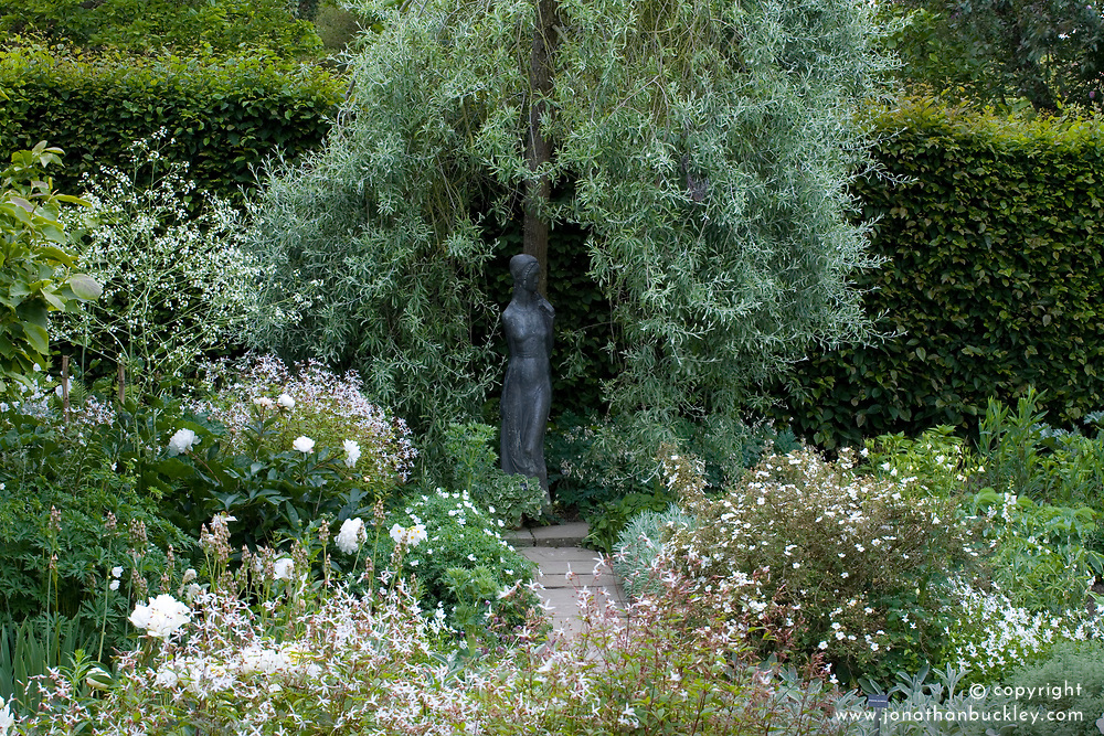 The White Garden at Sissinghurst Castle with a statue by Rosandic under a weeping pear tree