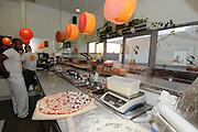 Israel, Tel Aviv, Pizza shop preparing the pizza ready base before baking