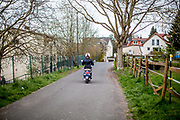 A woman passing by on a little motorcycle.