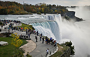SHOT 10/21/17 2:12:22 PM - Tourists take in the American Falls which is the second-largest of the three waterfalls that together are known as Niagara Falls on the Niagara River along the Canada–U.S. border. Unlike the much larger Horseshoe Falls, of which two-thirds is located in Ontario, Canada and one-third in the U.S. state of New York, the American Falls is entirely within the United States. The falls are viewable from a steep angle on the American side, where it is possible to approach to within several meters of the edge of the falls. One can view the falls from the bank of the river, as well as on Goat Island and Luna Island, which are accessible by a pedestrian bridge that crosses the rapids of the Niagara River upstream from the falls. Niagara Falls is famed both for its beauty and as a valuable source of hydroelectric power. Balancing recreational, commercial, and industrial uses has been a challenge for the stewards of the falls since the 19th century. (Photo by Marc Piscotty / © 2017)