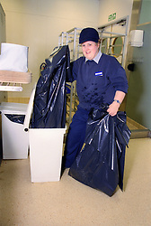 Woman with learning disability emptying rubbish bin,