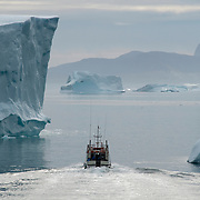 A boat near the icebergs of Greenland.