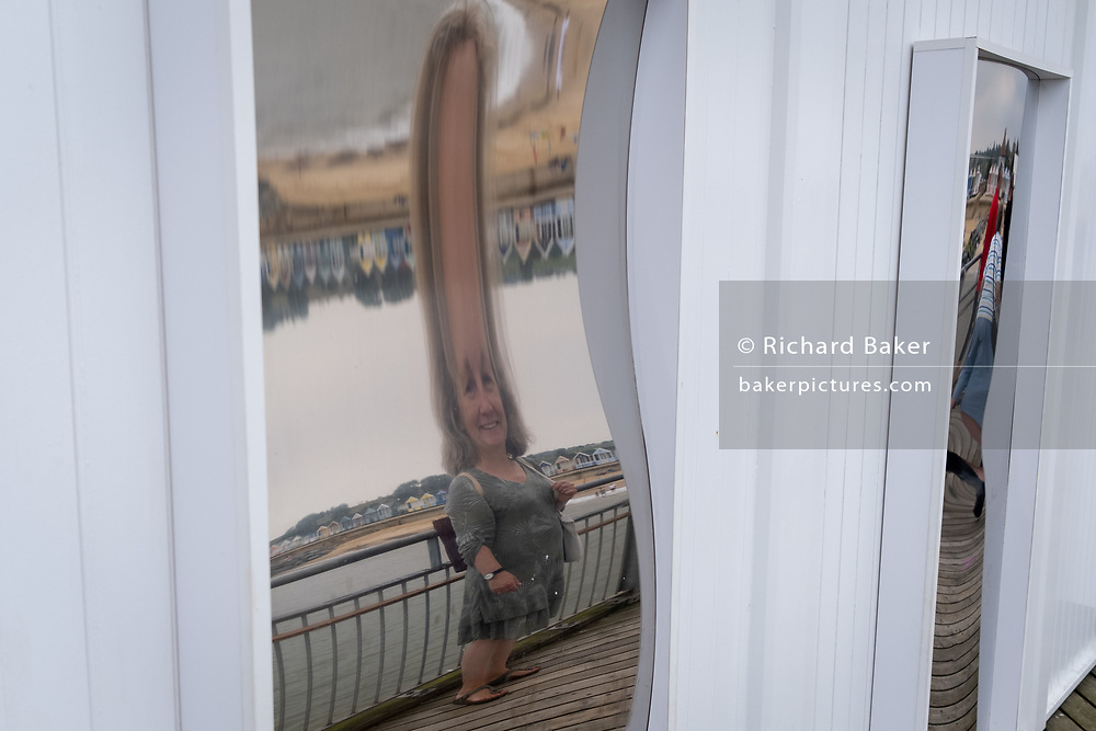 Faces and bodies are distorted by shaped mirrors on Southwold Pier, on 14th August 2020, in Southwold, Norfolk, England.