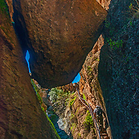 A hiker climbs out from the Bear Gulch Cave below the Reservoir in Pinnacles National Monument, San Benito County, California.