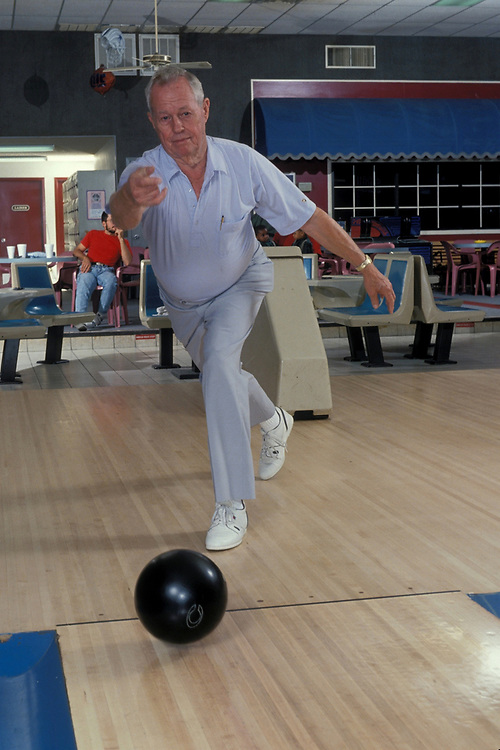 Elderly male bowling at bowling alley in Marble Falls, Texas.  Model Release ©Bob Daemmrich /