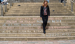 Woman walks down steps covered in feminist graffiti of Glasgow Royal Concert Hall in Glasgow, Scotland, UK