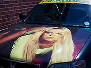 A bizzarely customized car has a photograph of a woman lying across the bonnet. London