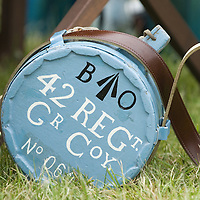 Old canteen with leather straps painted in blue with white writings, in the grass at an antique fair.<br />