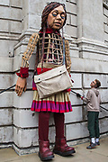 Little Amal, a giant puppet of a Syrian refugee girl fleeing conflict, stands against St Pauls Cathedral on 23rd October 2021 in London, United Kingdom. The 3.5-metre puppet, which is nearing the end of an 8,000km journey from the Turkish-Syrian border to Manchester in support of refugees, climbed the steps of St Pauls Cathedral to present a wood carving of a ship at sea from St Pauls birthplace at Tarsus in Turkey to the dean.
