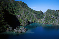 Aerial view of limestone karst shoreline with coral reefs below..Coron Island, Philippines.