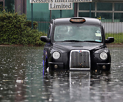 © Licensed to London News Pictures. 25/07/2021. London, UK. A London taxi sits abandoned in flood water in Stratford, east London. Heavy downpours and thunder and lightning have caused flooding in some parts of the UK today.. Photo credit: Kois Miah/LNP