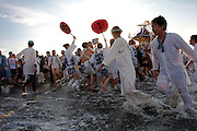 Mikoshi are carried into the sea during the Hamaorisai Matsuri that takes place on Southern Beach in Chigasaki, near Tokyo, Kanagawa, Japan Monday July 20th 2009. The festivals marks the celebration of Marine Day and the rescuing of a divine image that was washed ashore in the area. Over thirty Mikoshi or portable shrines are carried through the night from surrounding shrines to arrive on the beach for sunrise. There they are blessed and then carried into the surf to purify them.