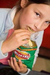Child eating packet of crisps,