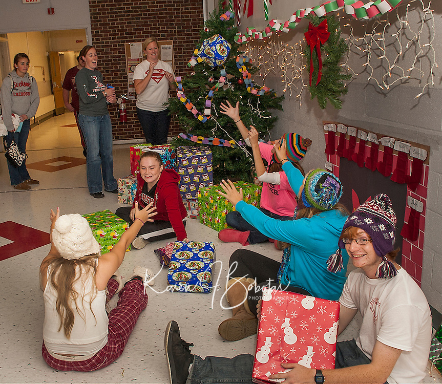 "Junior class advisors Suzanne Kiefer and Amy Bennett toss Kylee Powers, Becca Kendall, Emina Karabegovic, John Hammond and Nicole Bogert (in the white cap) gifts as they deck the halls of Laconia High School with their ""Christmas"" holiday theme for Friday's Homecoming festivities.    (Karen Bobotas/for the Laconia Daily Sun)"
