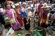 China's women who hail from the cultural minorities buy and sell in the Menghan Sunday Market in Xishuangbanna, near the Burma border. China is green and leafy in the spring with cucumbers, squash, green onions, long beans, leeks, and bok choy..(Supporting image from the project Hungry Planet: What the World Eats).