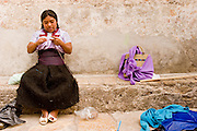 27 APRIL 2005 - SAN CRISTOBAL DE LAS CASAS, CHIAPAS, MEXICO: A Mayan Indian woman makes handicrafts to sell to tourists in the market in San Cristobal de las Casas, Chiapas. San Cristobal de las Casas is an important tourist destination for those who want to visit Mexican colonial cities. San Cristobal is the center of the Chiapas highlands and an important indigenous community. Fear of political violence in the area has diminished in recent years and the tourism industry has rebounded as a result.  PHOTO BY JACK KURTZ
