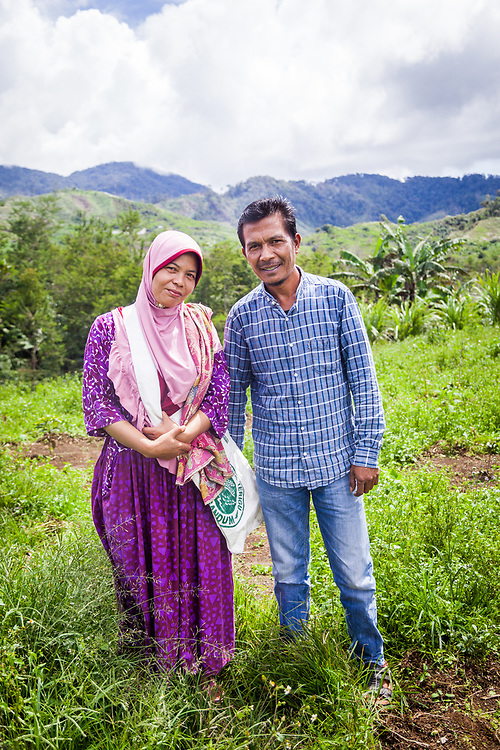 Ibu Suslaini (39) and husband Pak Saleh (42( pose for a portrait.  Ibu Suslaini has been a member of Kokowa Gayo since 2014.  The biggest challenge as a farmer are insects that attack coffee plants and cherries.  As a member of Kokowa Gayo her earnings are more stable.  She also receives support such as training, tools, and basic daily essentials.  People should buy Fair Trade because the quality of the coffee is guaranteed and tastes great.